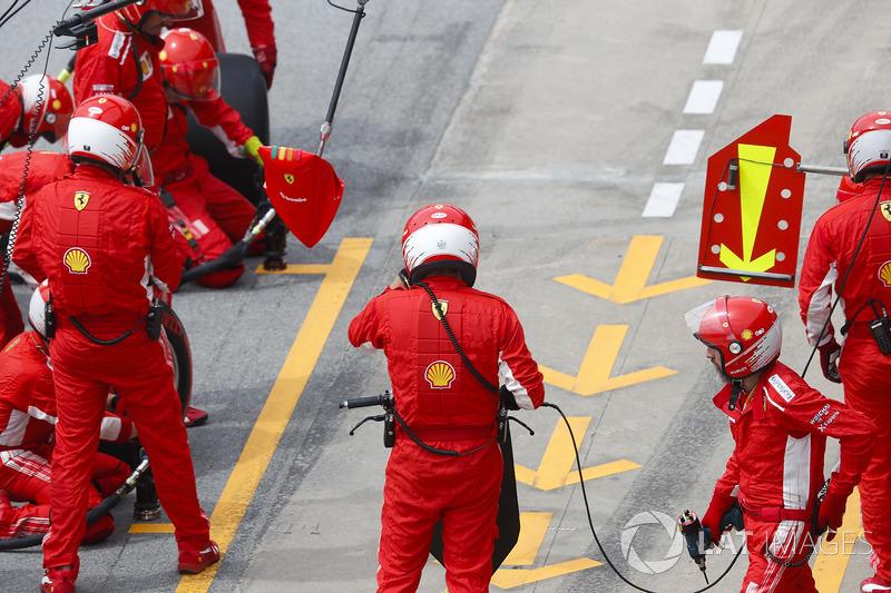 Ferrari mechanics wait for Kimi Raikkonen, Ferrari SF71H, to make a pit stop