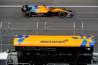 Carlos Sainz Jr., McLaren MCL34, passes in front of the McLaren pit gantry