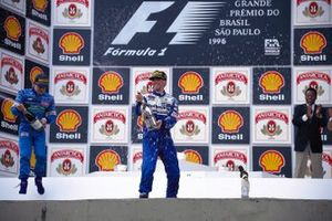 Damon Hill celebrates victory on the podium with Jean Alesi and Brazilian football legend Pele