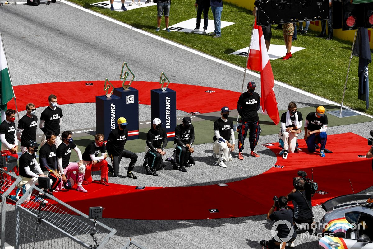 Los pilotos se arrodillan en la parrilla antes de la salida.