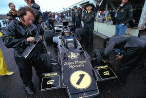 Ronnie Peterson waits in his Lotus 72E Ford, overseen by Colin Chapman