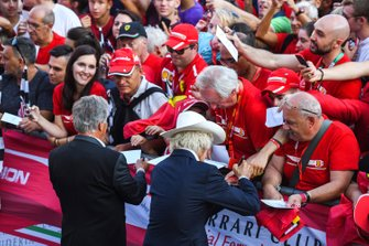 Mario Andretti and Arturo Merzario sign autographs for fans