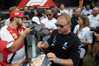 Valtteri Bottas, Mercedes AMG F1 and Lewis Hamilton, Mercedes AMG F1 signs a autographs for a fans