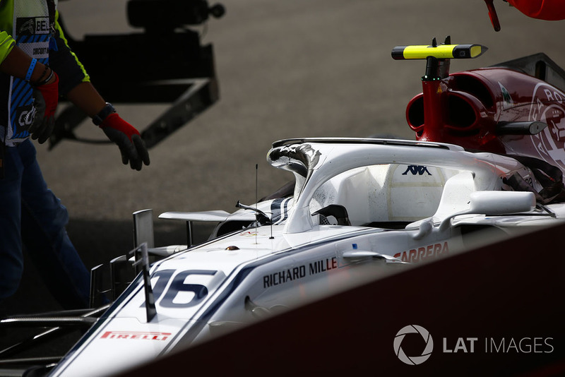 Marshals remove the damaged car of Charles Leclerc, Sauber C37, after a crash on the opening lap