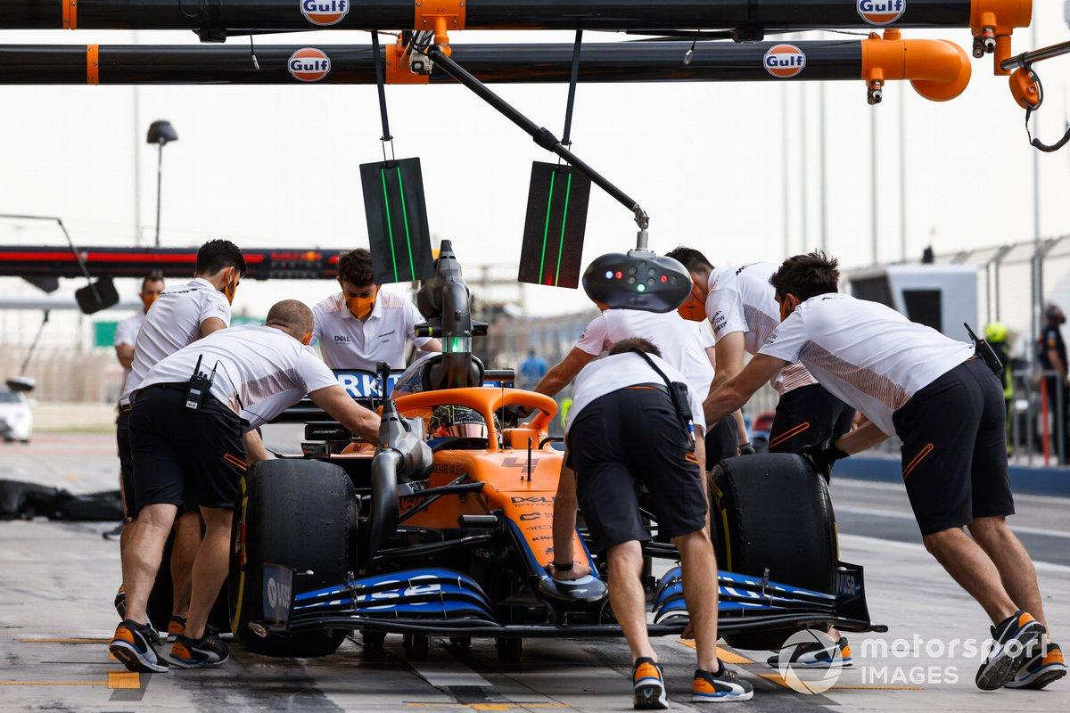 Los mecánicos empujan el coche de Lando Norris, McLaren MCL35M, en los boxes