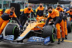 Mechanics push the car of Lando Norris, McLaren MCL35M, on the grid