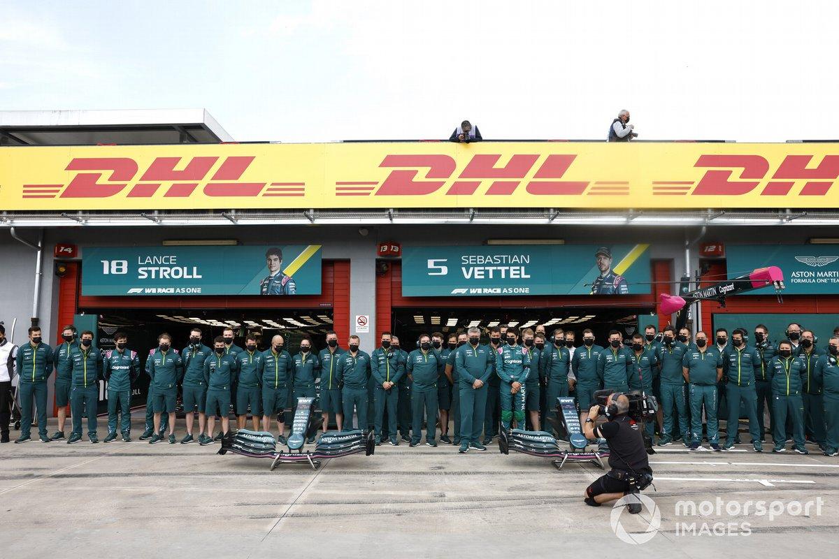 El equipo Aston Martin se pone de pie para una foto de equipo en el pit lane