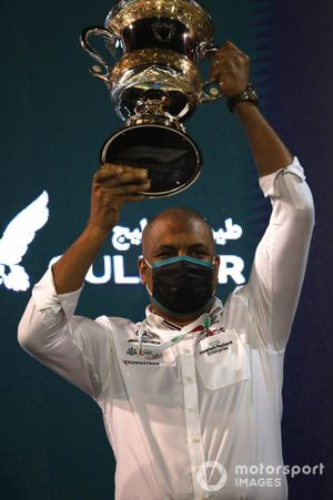 Mercedes team member on podium with trophy
