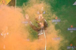 Lewis Hamilton, Mercedes, 2e plaats, tilt zijn trofee op als oranje rook het podium overspoelt