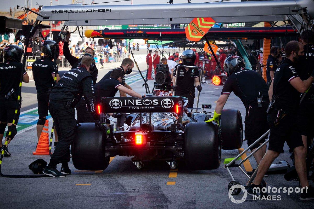 Los mecánicos llevan el coche de Lewis Hamilton, Mercedes W12, desde el pit lane