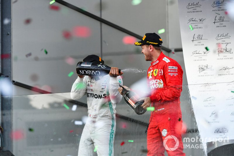 Lewis Hamilton, Mercedes AMG F1, 2nd position, and Sebastian Vettel, Ferrari, 3rd position, spray Champagne at each other on the podium
