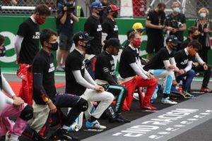The drivers take a knee and stand in support of the End Racism Campaign before the race