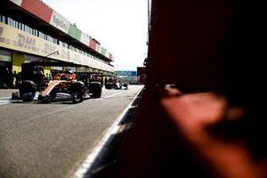 Lando Norris, McLaren MCL35, Carlos Sainz Jr., McLaren MCL35, in the pit lane