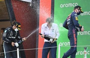 Lewis Hamilton, Mercedes, 1st position, the Mercedes trophy delegate and Max Verstappen, Red Bull Racing, 2nd position, spray Champagne on the podium