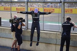 Pole man Lewis Hamilton, Mercedes, jumps down from the catch fence