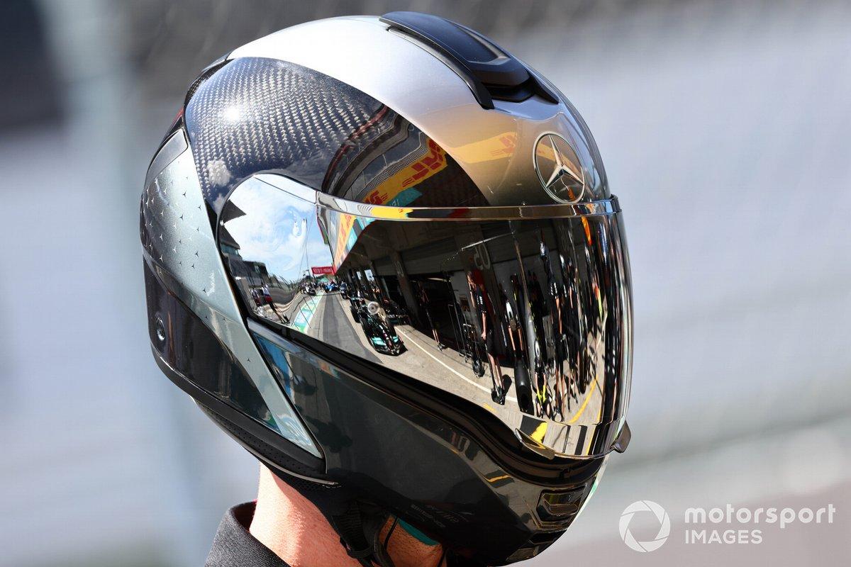 El coche de Lewis Hamilton, Mercedes W12, reflejado en el casco de un mecánico