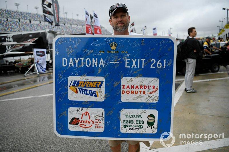 Fan with autograph board in paddock.