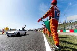 Marshals langs de baan wanneer Stoffel Vandoorne, McLaren, passeert tijdens de rijdersparade
