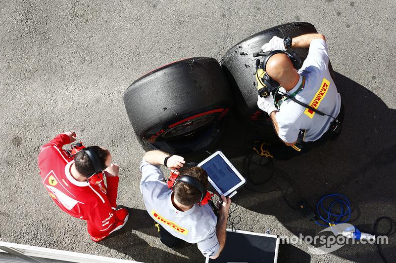 Ferrari y Pirelli empleados trabajan al lado de algunos neumáticos súper blandos