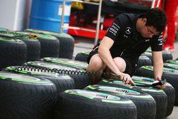 Un mécanicien Mercedes AMG F1 Team travaille sur les pneus Pirelli