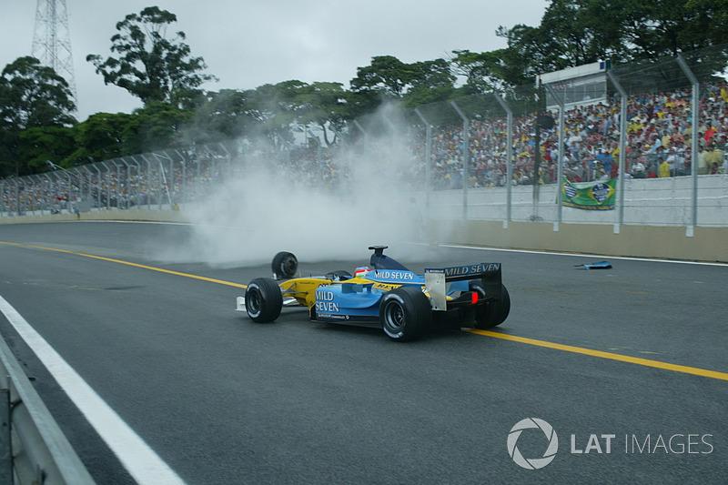 Гонщик Renault Renault F1 Team Ярно Трулли объезжает разбитую R23 Фернандо Алонсо