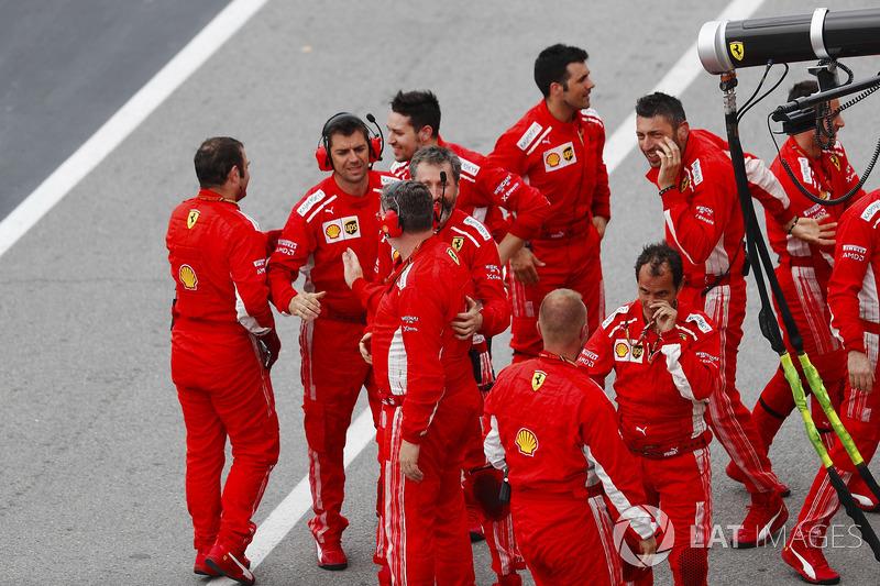 Ferrari team members celebrate the victory of Sebastian Vettel