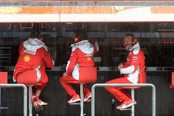 Des ingénieurs Ferrari sur le muret des stands