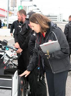 Cara Adams, chief engineer for Firestone Racing, inspects a tire on Josef Newgarden, Team Penske Chevrolet's car