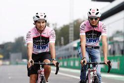 Esteban Ocon, Force India y Sergio Pérez, Force India, andan por el circuito en bicicleta
