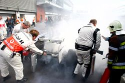McLaren mechanics help extinguish the fire on Rubens Barrichello, Brawn GP BGP001 Mercedes at Parc F
