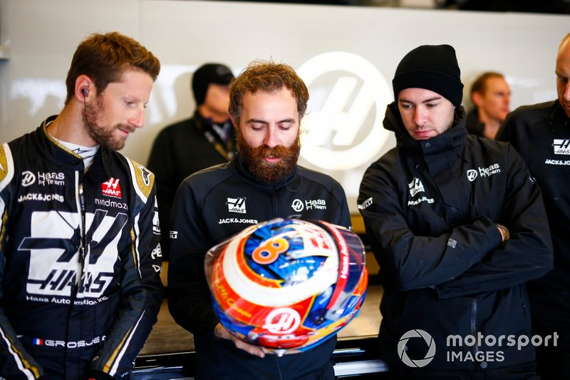 Romain Grosjean, Haas F1 Team, discusses his helmet design with a team mate