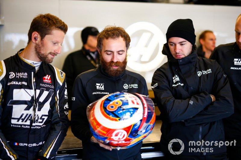 Romain Grosjean, Haas F1 Team, comenta el diseño de su casco con un compañero de equipo