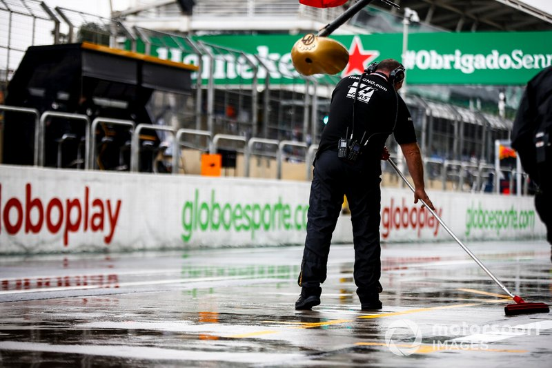 A Haas mechanic sweeps water from outside the garage
