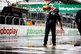 Un meccanico Haas spazza l'acqua fuori dal garage