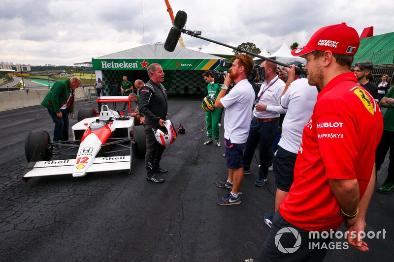 Sebastian Vettel, Ferrari looking at the McLaren MP4/4 whilst Martin Brundle, Sky TV speaks to the media