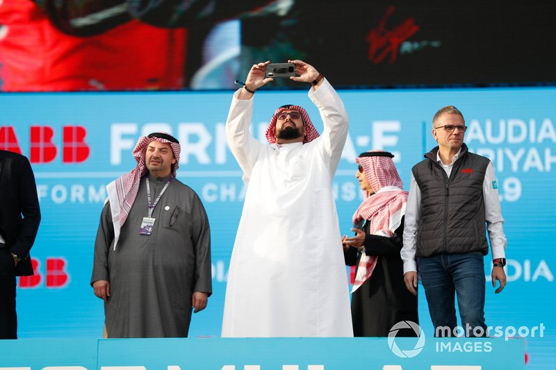 A Saudi VIP takes a photo from the podium