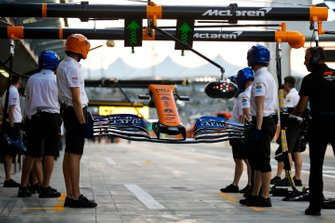 Mechanics holds a nose and front wing, and wait for Carlos Sainz Jr., McLaren MCL34, to make a pit stop.
