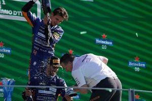 Lando Norris, McLaren, tweede plaats, schenkt champagne in terwijl Daniel Ricciardo, McLaren, eerste plaats, een shoey klaarmaakt voor Zak Brown, CEO, McLaren Racing, op het podium