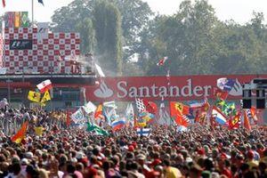 Tifosi flood the track beneath the podium to celebrate victory for Fernando Alonso, Ferrari
