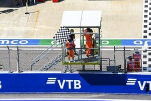 A marshal waves the chequered flag at the end of FP1