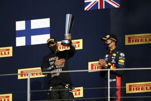 Lewis Hamilton, Mercedes-AMG F1, 1st position, with his trophy, and Alex Albon, Red Bull Racing, 3rd position, on the podium