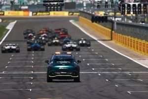 The Medical car persues as Max Verstappen, Red Bull Racing RB16B, and Lewis Hamilton, Mercedes W12, lead the field away at the start