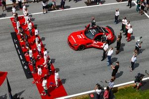 The drivers stand for the national anthem on the grid prior to the start