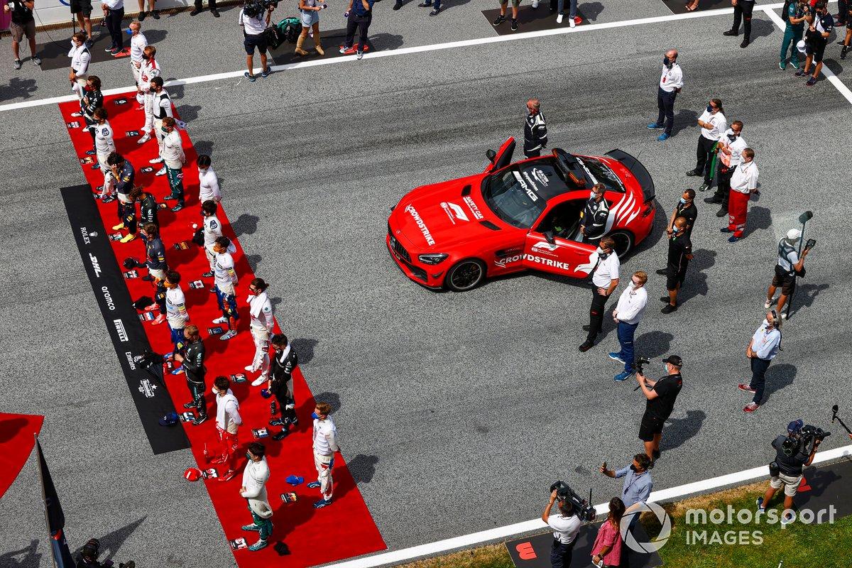 Los pilotos se ponen en pie para escuchar el himno nacional en la parrilla antes de la salida