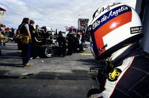 Elio de Angelis looks on as his mechanics work on his Lotus 95T Renault