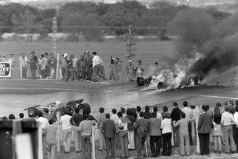 Los aficionados observan un coche en llamas mientras la acción continúa en la pista