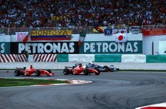 Rubens Barrichello, Ferrari F2001 takes the lead as Juan Pablo Montoya, Williams FW24 runs wide after being hit by Michael Schumacher, Ferrari F2001 at the first corner