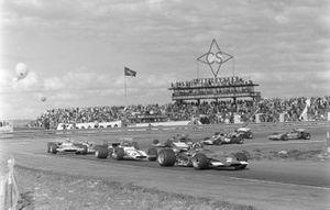 Jacky Ickx, Ferrari 312B, lidera a Jackie Oliver, BRM P153, y Henri Pescarolo, Matra MS120, con un grupo de coches detrás