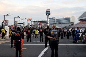 Los conductores y la tripulación se ponen de pie para el himno nacional