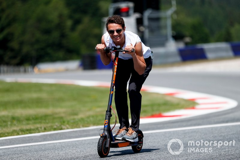 Lando Norris, McLaren walks the track on scooters